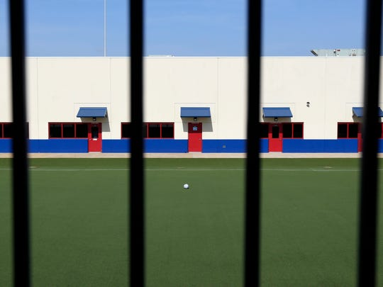 In this July 31, 2014, file photo, an artificial turf soccer field sits in the middle of the Karnes County Residential Center in Karnes City, Texas. The immigration detention facility has been retooled to house adults with children who have been apprehended at the border.