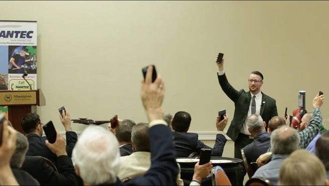 Manufacturing CEOs raise their smart phones during a presentation by York-based entrepreneur John McElligott at the MANTEC 2016 Business Growth Conference. McElligott plans to convert the Western National Bank Building in York into a computer programming training center.