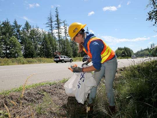Angela McCown, 15, of Bremerton, picks up litter along the side of southbound Highway 3 near the Trigger exit on Friday afternoon.