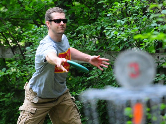 Tim Nelson of Green Bay holes out while playing disc golf at Pamperin Park in Howard on Sunday.