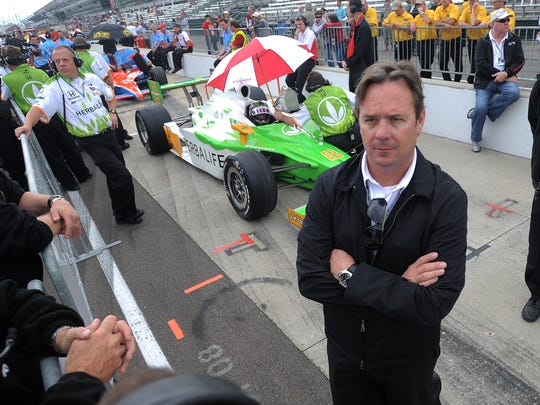 Team owner Jimmy Vasser looks as his driver Townsand Bell sit in his cr under an umbrella waiting out the rain for his chance to qualify for the 2009 Indianapolis 500 at the Indianapolis Motor Speedway.