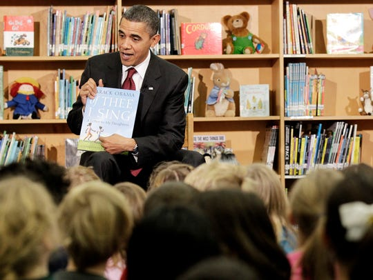 "President Obama holds up a book he authored, ""Of Thee"