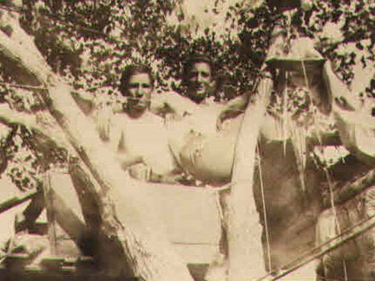 Doyle Gaither, left, and Robert Fogle attempt to break the tree-sitting record in the summer of 1930. Lighting equipment had been installed and a corps of aides were on hand to attend their needs.