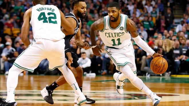 Boston Celtics guard Kyrie Irving (11) drives past San Antonio Spurs guard Patty Mills (8) who gets picked by center Al Horford (42) during the first half at TD Garden.