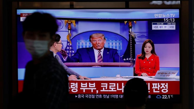 A man wearing a face mask walks near a TV screen reporting about U.S. President Donald Trump and first lady Melania Trump during a news program with a file image of Trump at the Seoul Railway Station in Seoul, South Korea, Friday. Trump said early Friday that he and Melania Trump have tested positive for the coronavirus.