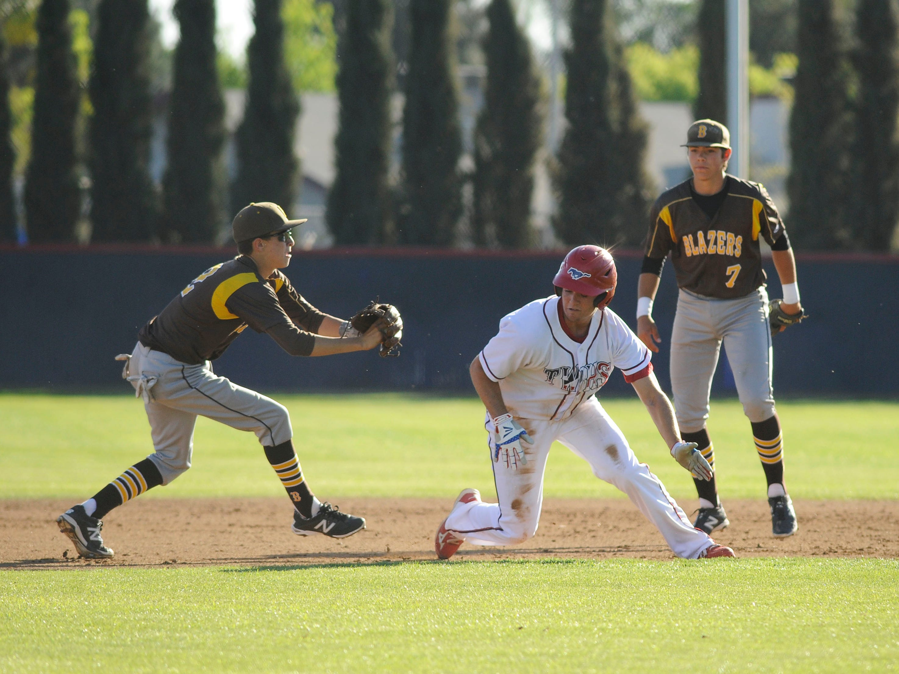 Tulare Western's Blake Costa, center, tries to avoid a tag by Golden West's Zac Legarretta, left, while Golden West's Wyatt Tilley watches during Thursday's game at Tulare Western.