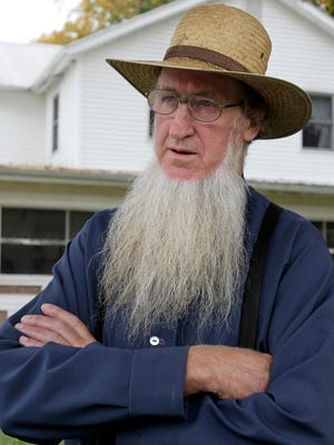 In this Oct. 10, 2011 file photo, Sam Mullet Sr. stands in the front yard of his home in Bergholz, Ohio. Mullet, the leader of a breakaway Amish group in Ohio convicted in hair- and beard-cutting attacks, is pushing to get his convictions overturned using arguments already rejected in court. An attorney for 72-year-old Samuel Mullet Sr. says Mullet's previous lawyer made mistakes during trial and in prior appeals. In a Monday, March 19, 2018 court filing, prosecutors say there were no errors that amounted to Mullet's rights to due process being violated, and a judge should reject his request. (AP Photo/Amy Sancetta, File)
