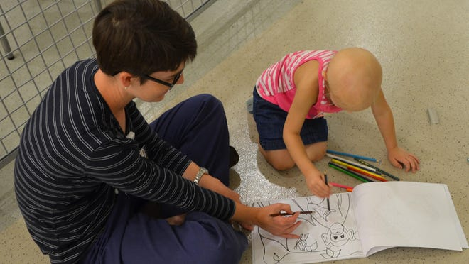 Child Life Specialist Jennifer Eddy helps a cancer patient get involved in painting.