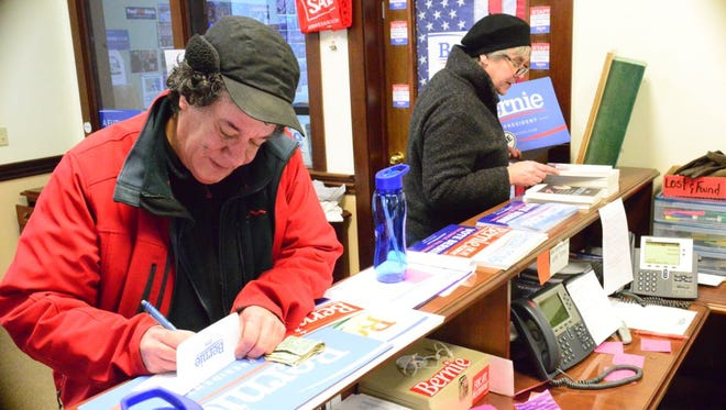 Bernie Sanders supporters Mary Ann Vuillemin and Fred Blakely of Calais pick up signs and bumper stickers at the campaign's Burlington heaquarters Saturday afternoon.