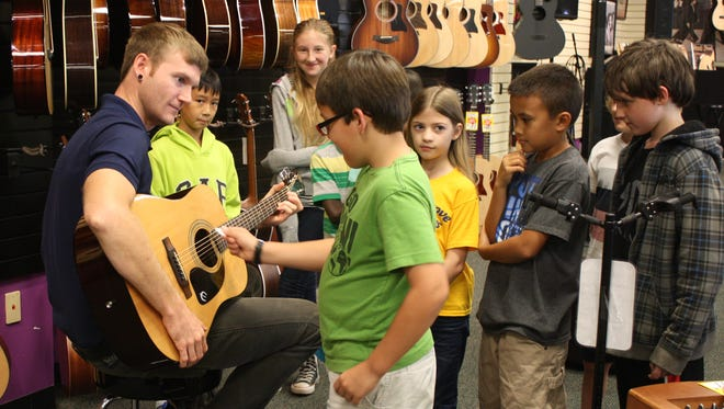 Tony Johnson, BAM guitar instructor and a local performer, demonstrated various ways to strum a guitar and then students took turns making sound.