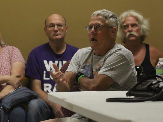 Neighborhood resident Dale Millard gestures while voicing