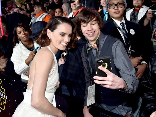Daisy Ridley poses with a fan at the world premiere
