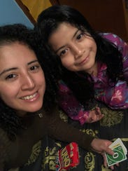 Roxana Jimenez plays cards with her 8-year-old daughter