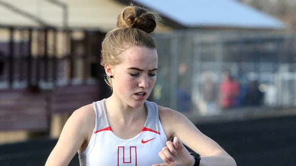 Holliday's Leah Bullinger checks her time as she competes in the 3200 meter run at the Seymour Track Meet Thursday, March 8, 2018, in Seymour.