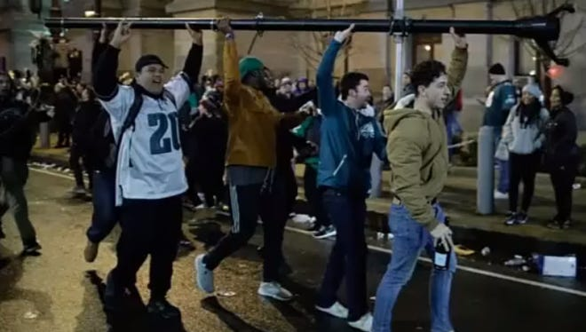 Fans carry a vandalized pole as they celebrated the Philadelphia Eagles' Super Bowl win.