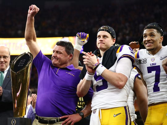 Jan 13, 2020; New Orleans, Louisiana, USA; LSU Tigers head coach Ed Orgeron raises his fists as he celebrates with quarterback Joe Burrow after a victory against the Clemson Tigers in the College Football Playoff national championship game at Mercedes-Benz Superdome. Mandatory Credit: Matthew Emmons-USA TODAY Sports