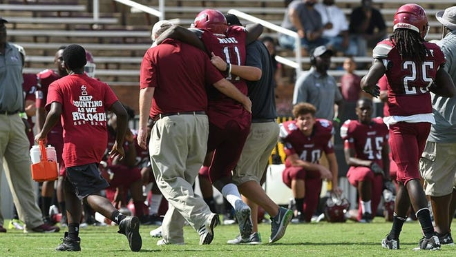 Charles Moore is helped off the field by Louisville's coaching staff during Saturday's jamboree game against Starkville.
