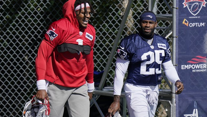 New England Patriots quarterback Cam Newton (1) and defensive back Terrence Brooks (25) step on the field at the start of an an NFL football training camp practice, Sunday, Aug. 30, 2020, in Foxboro.