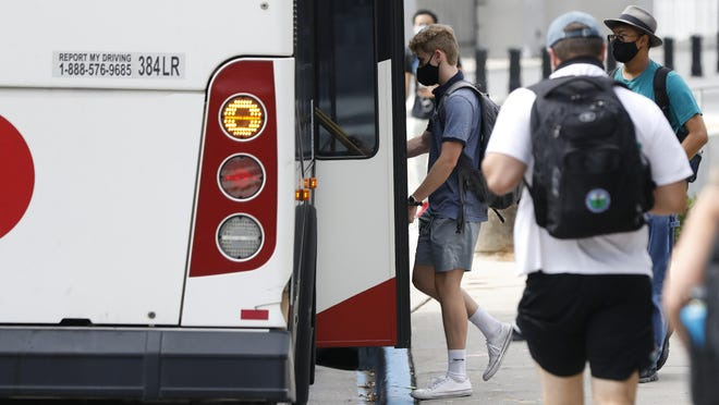 University of Georgia students catch a bus at the Tate Student Center last month. Clarke County's COVID-19 cases have spiked since students returned to fall semester classes Aug. 20.