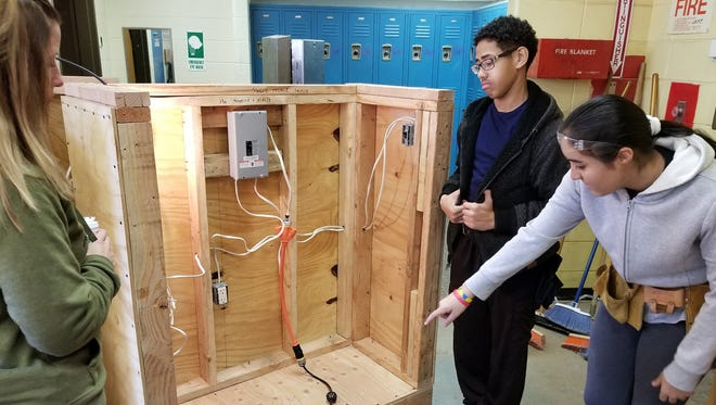 MCVTS Career Choices students Steven Sanchez of Perth Amboy and Ashley Lopez of Avenel show their construction technology project to Detective Joelle Slossberg of the Woodbridge Police.