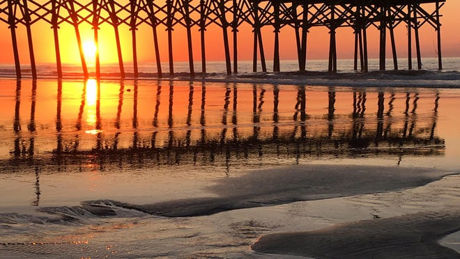 The sun rises on a new day at a pier in Myrtle Beach