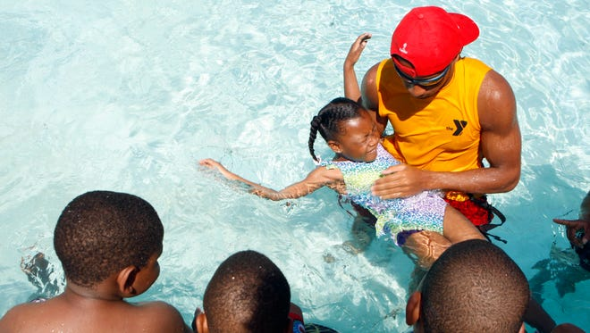 Dawud Bibbyah teaches children, including Haylee McCullough,  to swim at the YMCA in Whitehaven, Tenn., on, June 20, 2014.