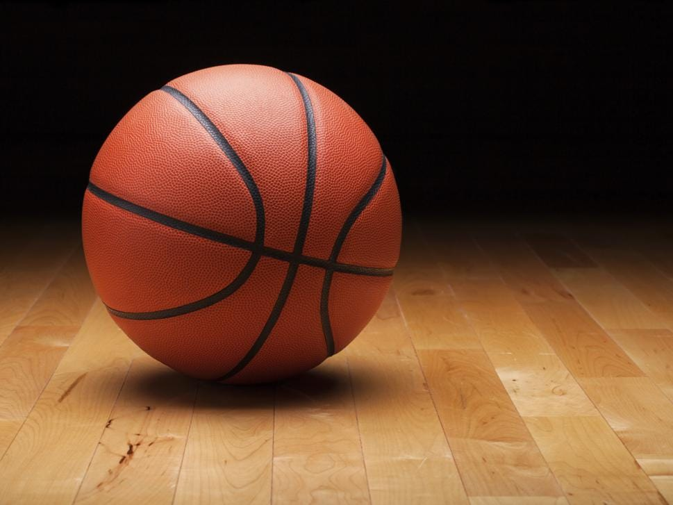 Basketball with dark background on a wood gym floor