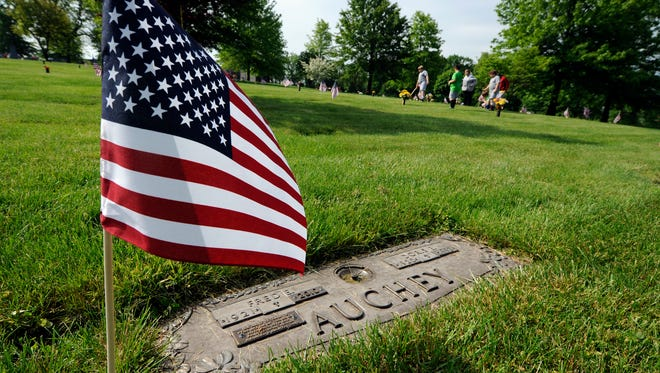 Elementary students from St. Rose of Lima School place flags on the graves of veterans at Holy Savior Cemetery in Manchester Township in preparation for Memorial Day, Monday, May 23, 2016. John A. Pavoncello photo