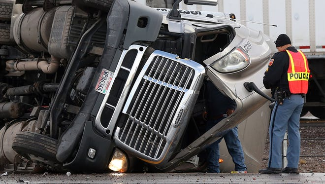 An El Paso police officer stands nearby while the driver of an overturned tractor-trailer steps up to look inside the cab along I-10 East about a half mile before the Trans Mountain Road overpass Thursday morning in West El Paso. A police officer on the scene said the accident may have been weather-related as overnight rains created slick roadway conditions. There were no apparent injuries. The accident backed up traffic on the East bound side about three miles.