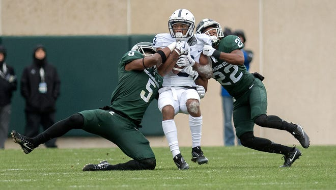 Michigan State's Andrew Dowell, left, and Josiah Scott tackle Penn State's DeAndre Tompkins in the first quarter Saturday.