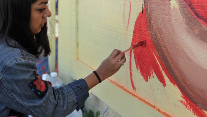 Artist Mikayla Gutierrez paints red on her project during the Queens of Style 2018 International Woman's Day art festival hosted by the Urbanist Collective at the old lumber yard in Visalia on March 17, 2018.