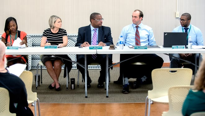 Lansing Housing Commission board President Tony Baltimore, center, Executive Director Martell Armstrong, far right, and board members, from left, Tamara Warren, Bethany Deschaine and Ryan Robinson hold a regular meeting on Wednesday, June 27, 2018, in the front office of the LaRoy Froh housing complex in Lansing.