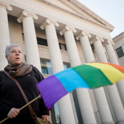 "Minoo Vafai holds a rainbow flag during the ""Remove"