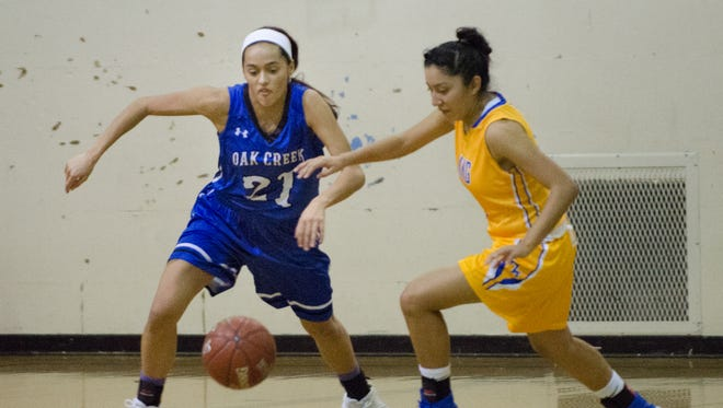 Oak Creek guard Kassandra Bartek and Milwaukee King guard Annaly Garcia chase down a loose ball.