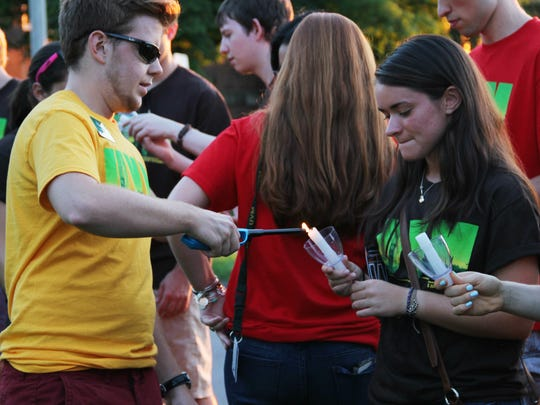 University of Vermont senior Patrick Maguire lights the candle of incoming student Samantha Albee of Framingham, Mass., during the university's new student convocation on Sunday.
