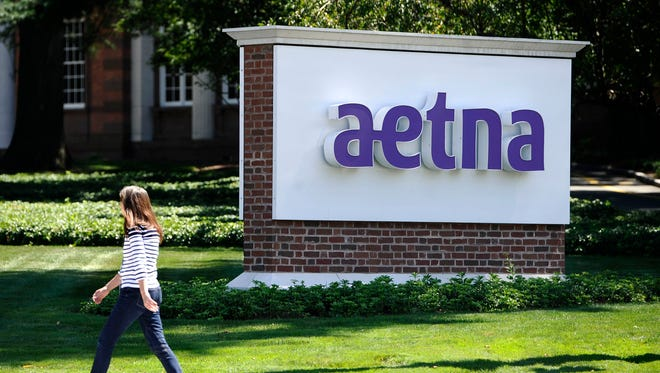 A pedestrian walks past a sign for health insurer Aetna Inc., at the company headquarters in Hartford, Conn.