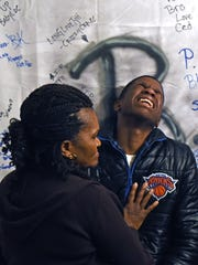 Marcus Moody Hartley cries after writing a message to close friend Tyimer Bright in front of a memorial sheet at the boy's East Camden home.