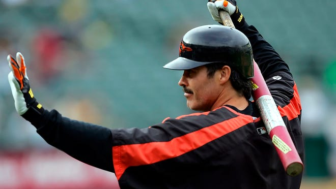 """FILE - In this Aug. 15, 2005, file photo, Baltimore Orioles' Rafael Palmeiro waves to fans as he prepares to take batting practice for the team's baseball game against the Oakland Athletics in Oakland, Calif. Palmeiro says he has agreed to play with his son for the independent Cleburne (Texas) Railroaders at age 53. Palmeiro told the Dallas Morning News in a text Tuesday that he is looking forward to joining the second-year American Association team and will be teammates with his 28-year-old son Patrick. """"Nobody gave me a chance to go to spring training, so I will just take this path,"""" Palmeiro said in the text. (AP Photo/Marcio Jose Sanchez, File)"""