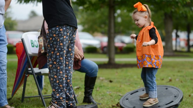 Kambrie Hughes, 2, practices her balance at Child Health Day at Liberty Garden Park on Friday afternoon.