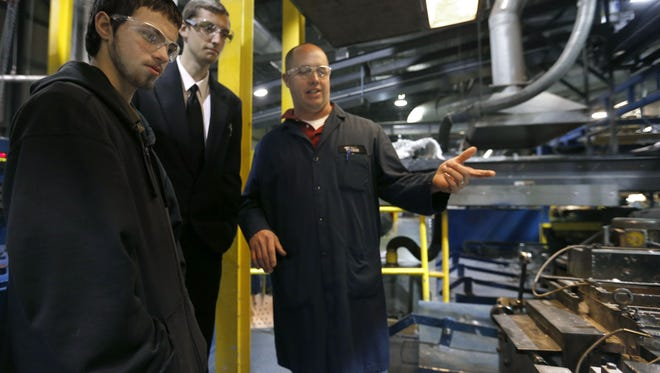 In 2015, the Greater Ozarks Centers for Advanced Professional Studies, students Jay Ripplinger (left), 16, and Tyler Gerischer (center), 17, talk with Nathan Clemons, a production manager at NorthStar Battery, about the battery making process.
