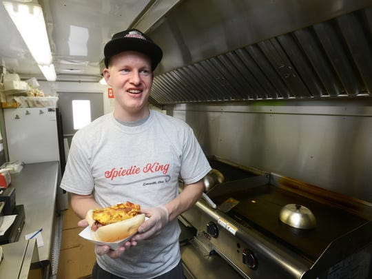 Mike Coveney holds a mac and cheese hot dog in the Spiedie King food truck. The truck offers a variety dishes, including its specialty, the Classic Spiedie chicken sandwich.