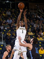 Michigan's Charles Matthews shoots over Grand Valley State's Zach West in the first half of an exhibition Friday, Nov. 3, 2017 at Crisler Center in Ann Arbor.
