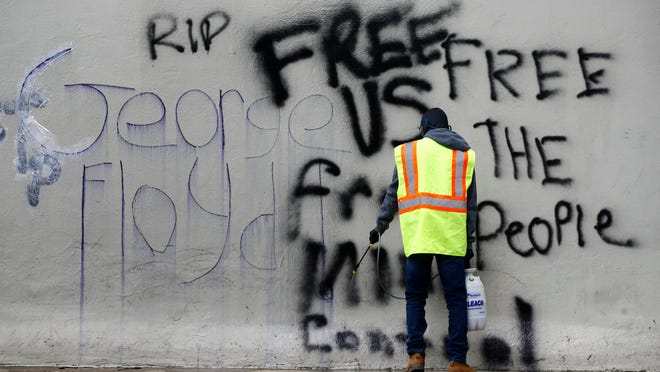 A worker removes graffiti from a building on June 2 in Washington, following protests over the death of George Floyd, who died after being restrained by Minneapolis police officers.