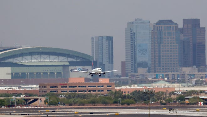 Heat waves ripple across the tarmac at Sky Harbor International Airport with downtown Phoenix in the background as an airplane lands on June 20, 2017 in Phoenix.