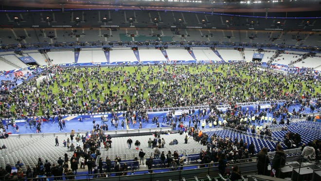 Spectators wait on the pitch of the Stade de France stadium  after France played Germany in a soccer friendly.
