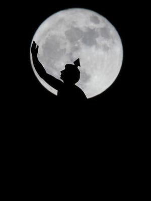 The supermoon rises over a statue of Mercury atop of the Union Station Hotel clock tower Monday, Nov. 14, 2016, in Nashville, Tenn.