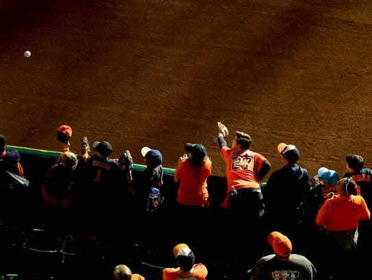 Fans try for a fly ball during batting practice before