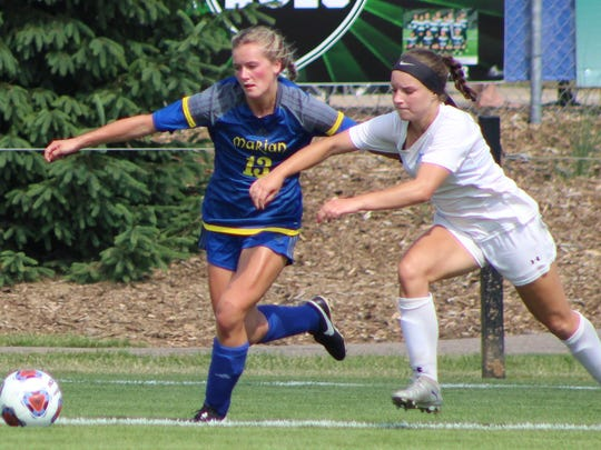 Marian midfielder Grace Kinna (13) battles Forest Hills Northern defender Sophie Renucci late in the first half of Saturday's Division 2 state championship game.