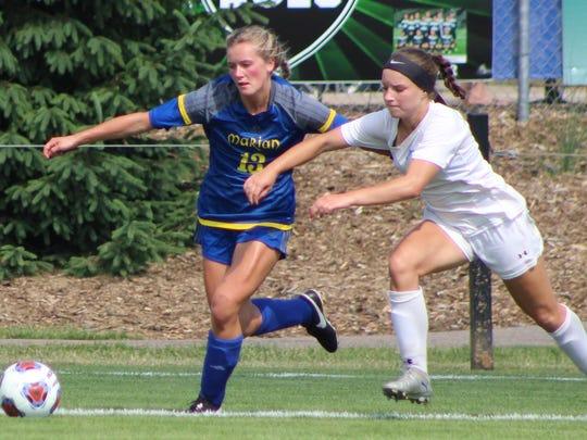 Marian midfielder Grace Kinna (13) battles Forest Hills