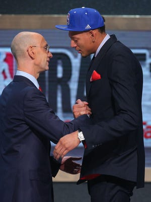 Jun 26, 2014; Brooklyn, NY, USA; Isaiah Austin (Baylor) shakes hands with NBA commissioner Adam Silver after being selected as an honorary draft pick by the NBA during the 2014 NBA Draft at the Barclays Center. Austin was diagnosed with Marfan Syndrome ending his career.